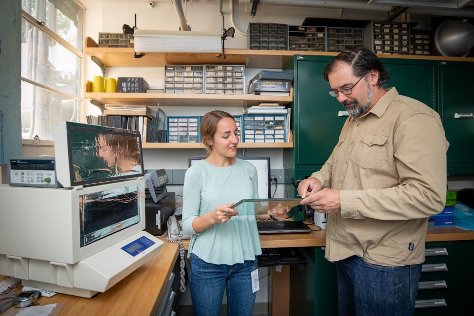 Hannah Moring and Howdy Goudey prepare to test the thermal conductivity of a vacuum insulated window pane sample using the LaserComp machine (shown, left).