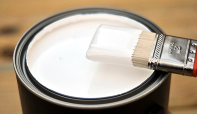 A paint brush resting on the edge of a can containing white paint.