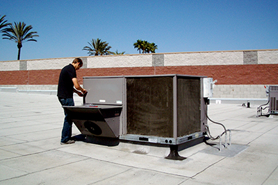 A scientist works on a rooftop air conditioner.