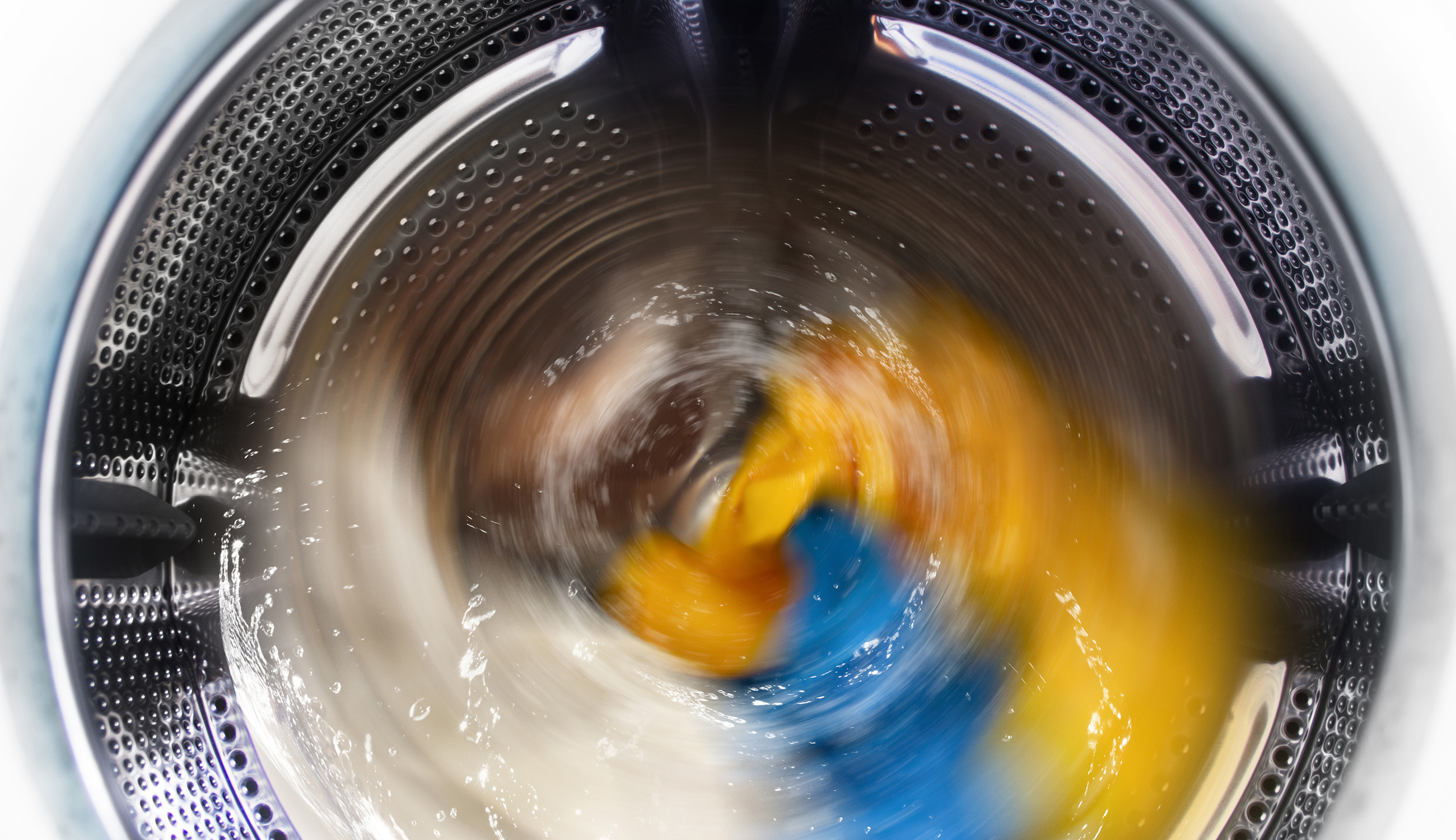View inside the washing machine while washing laundry. Splashing water.
